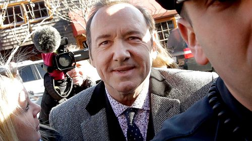 Kevin Spacey smiles as he arrives at Nantucket District Court.