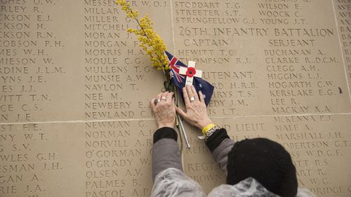 A woman holds up a small cross and an Australian flag to a wall bearing the names of the missing at the end of an Armistice ceremony at the World War I Australian National Memorial in Villers-Bretonneux, France, Sunday, Nov. 11, 2018.