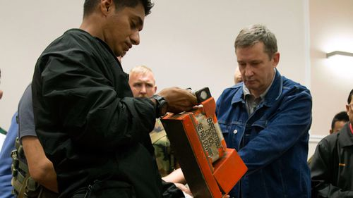 The black box is handed over to the Malaysian expert. (AAP)