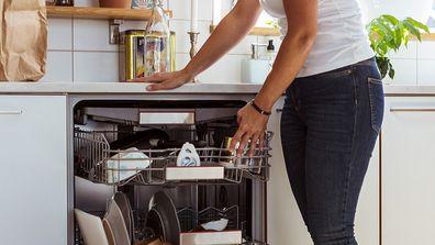 Woman doing housework emptying dishwasher