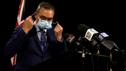 South Australian Premier Steven Marshall takes his mask off to brief the media on COVID-19.