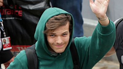 Louis Tomlinson of One Direction waves to fans after touching down in Sydney on Tuesday. (Getty)