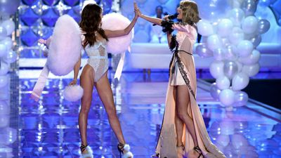 Taylor Swift gives Lily Aldridge a high-five during the Victoria's Secret Fashion Show in London. (AAP)