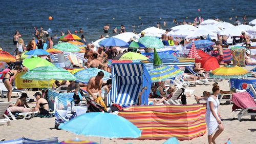 People enjoy the warm temperatures and bright sunshine as they crowd a beach in the Baltic Sea resort of Miedzyzdroje, northwestern Poland. (AAP)