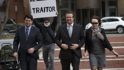 Paul Manafort (centre) is heckled as he walks into court.