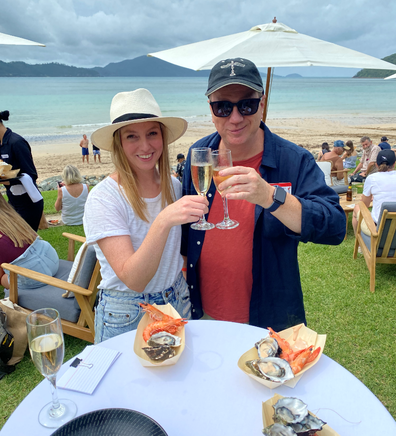 Guests of Qantas' Hamilton Island Mystery Flight relax with Champagne on the beach-facing lawn.