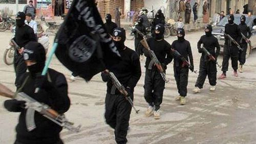 Islamic State fighters parade through the streets of Mosul. (AP)