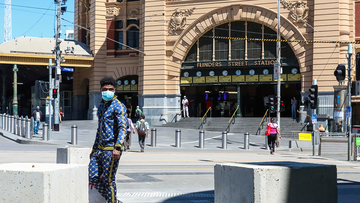 A man wearing a mask is seen walk past Flinders Street Station in Melbourne, Australia, Wednesday, Oct. 28, 2020. (AP Photo/Asanka Brendon Ratnayake)