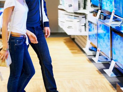 Young couple shopping for a TV