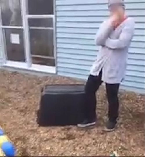 The staff member appears to be laughing as the toddler is stuck under the container. (KCCI)