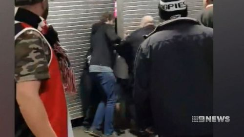 A man can be seen punched and pushed into a closed shop front. (9NEWS)
