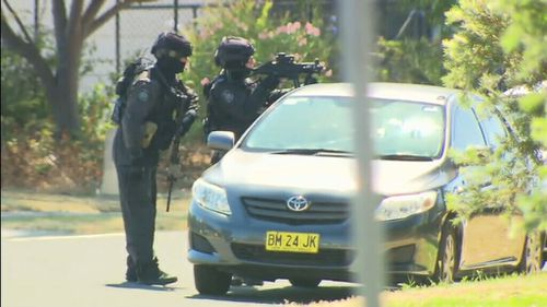 Police surrounding the sign factory. (9News)
