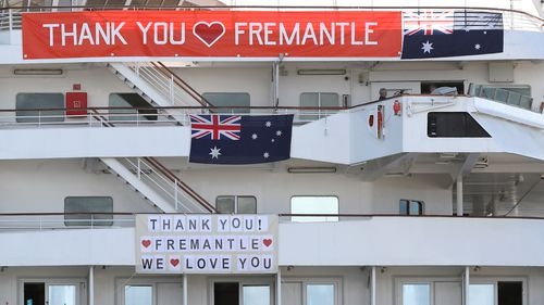 "The MV Artania is seen with ""Thank You Fremantle"" banners and Australian flags positioned on the side of the vessel while berthed at the Fremantle Passenger Terminal"