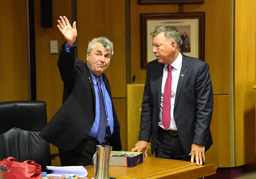 Cr David Pahlke waves goodbye as acting Mayor Wayne Wendt (right) looks on following the Ipswich City Council's final meeting at the Ipswich City Council Chambers