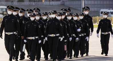 Chinese security personnel wearing protective masks march through Tiananmen Square during a national mourning to victims of COVID-19 on April 04, 2020 in Beijing, China.