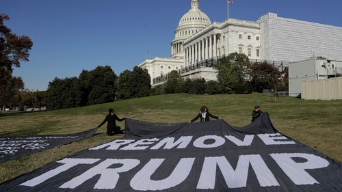 Demonstrators kneel near large banners on the lawn adjacent to the US Capitol.