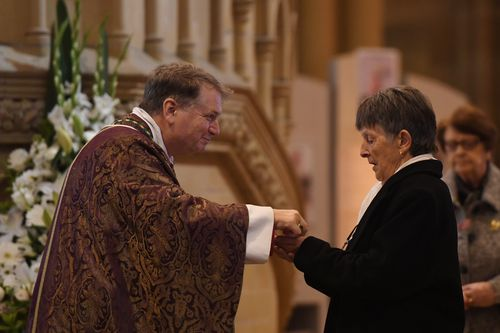 Catholic Archbishop of Sydney Anthony Fisher delivers communion to Pauline Johnson, the wife of John Richard Johnson. (AAP)