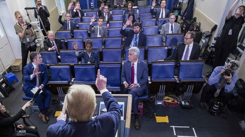 Donald Trump takes questions from a sparsely attended White House press conference. Journalists are required to be seating well apart from each other.