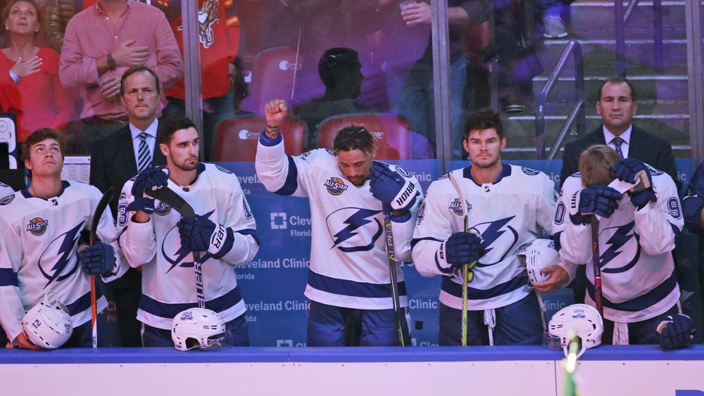 NHL's Tampa Bay forward JT Brown raises fist in silent protest during US anthem
