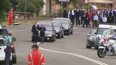 A sombre procession stretched several hundred metres behind Hughes' hearse. (9NEWS)