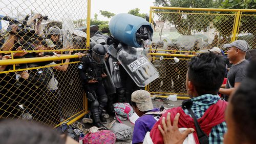 More than a hundred Central American migrants have forced their way through a customs gate at the Guatemalan border town of Tecun Uman to request passage into Mexico.