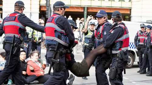 An animal rights protester who had blocked the intersections of Flinders and Swanston Street in Melbourne is removed by police.