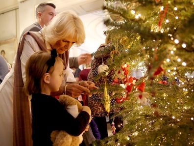 Camilla, Duchess of Cornwall decorates the Clarence House Christmas tree with children from various London charities in 2017.