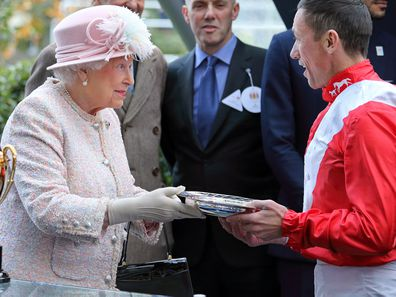 Queen Elizabeth II presents jockey Frankie Dettori with his prize for winning the Queen Elizabeth II Stakes at Ascot Racecourse on October 21, 2017.