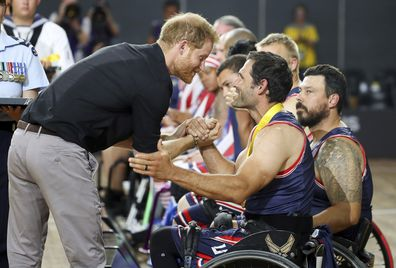 Britain's Prince Harry congratulates a member of the United States wheelchair basketball team after winning the gold medal in the finals during day eight of the Invictus Games Sydney, Australia, Saturday, Oct. 27, 2018.