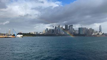 A rainbow in Sydney Harbour today, with Centrepoint Tower and the Opera House in the background.