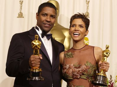 Actor and Actress in a Leading Role winners Denzel Washington and Halle Berry pose with their Oscars backstage in 2002.