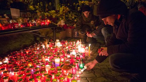 People light candles by a floral tribute for the victims of a fire in a multi-story shopping center in the Siberian city of Kemerovo. (AP).