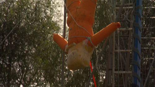 Godwin hangs a manikin in his backyard.