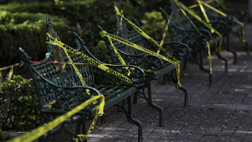 Caution tape is looped around park benches to discourage people from sitting on them in the main plaza of Coyoacan, in Mexico City, Saturday, April 4, 2020.