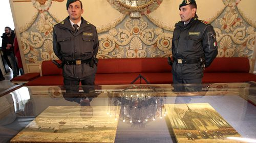"Two Italian policemen of the Guardia di Finanza (Financial Police) stand guard by the two recently recovered stolen paintings by late Dutch artist Vincent Van Gogh entitled ""Congregation Leaving the Reformed Church in Nuenen"" and ""The Beach At Scheveningen During A Storm"""