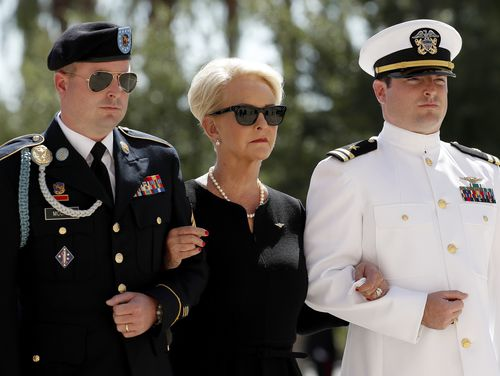 Cindy, escorted by sons, Jack McCain, right, and Jimmy McCain, following the casket.