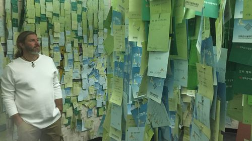 Cameraman Greg Martini looks at messages of hope from South Koreans. (Brett McLeod)