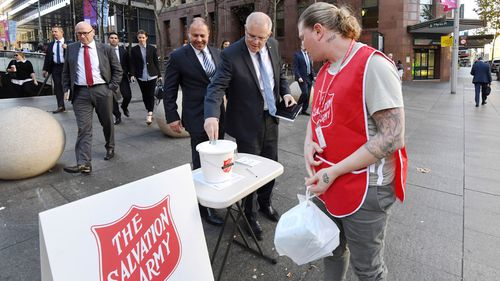 Scott Morrison, Josh Frydenberg meet with the Reserve Bank Governor Philip Lowe. Photo shows, Scott Morrison donates a $10 note into a Salvation Army collection bucket