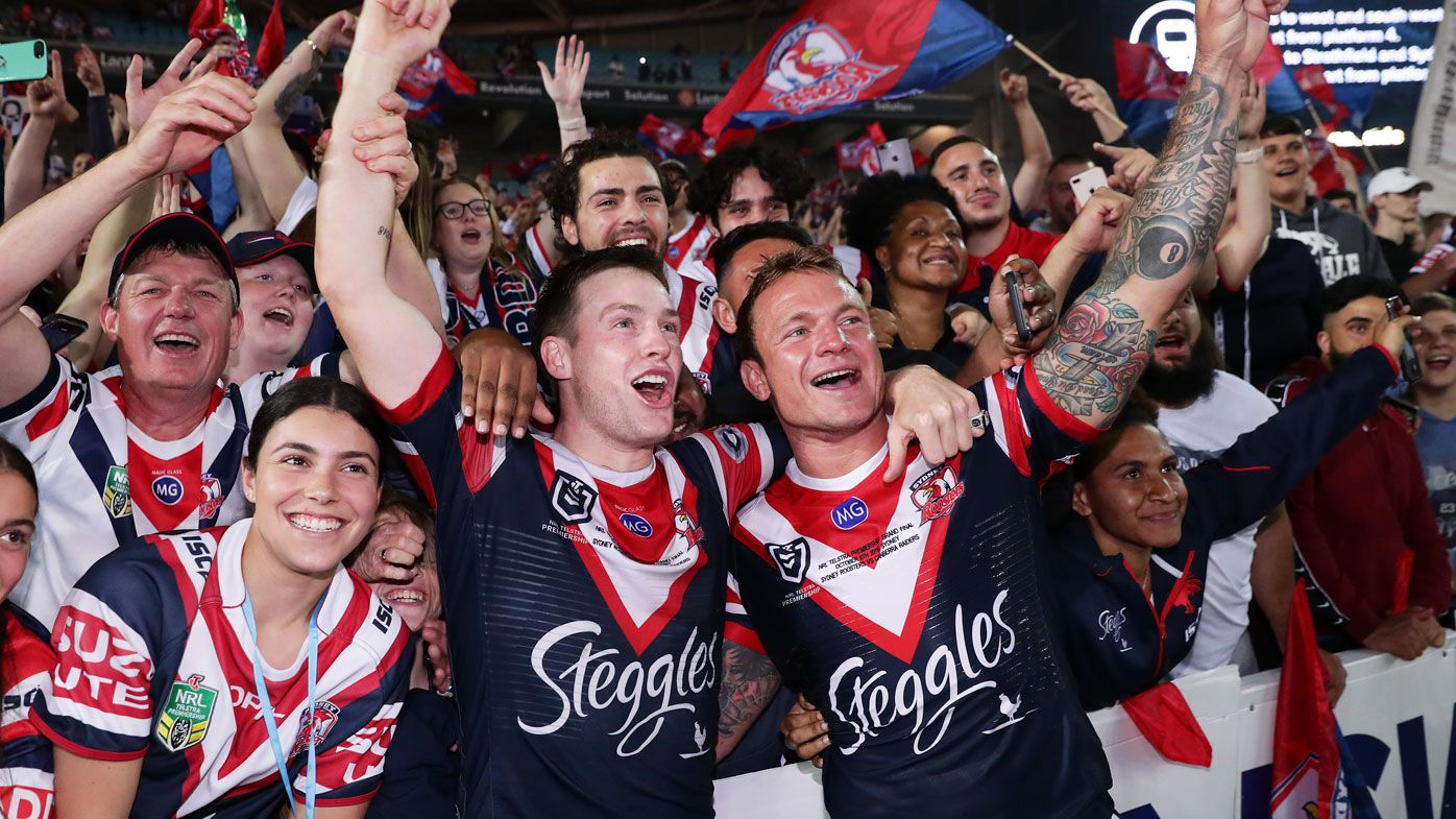 Luke Keary (L) and Jake Friend (R) of the Roosters celebrate victory with fans