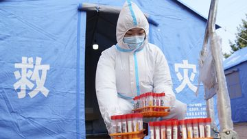 A worker in protective clothing handles COVID-19 test samples in Bayan County of Harbin city in northeastern China's Heilongjiang Province.
