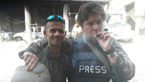 Owen Holdaway smokes a celebratory cigar with his photographer friend.