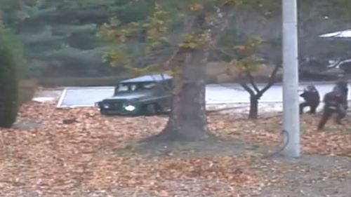 The solider is pursued by North Korean soldiers as he runs from the jeep. (AAP)