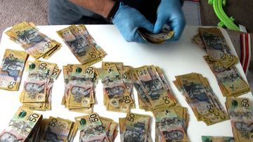 A NSW Police Officer counts cash, which allegedly totalled more than $50,000.