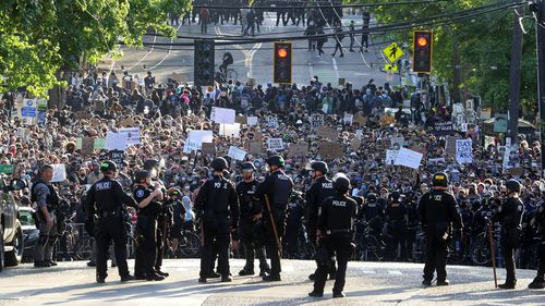 In this June 1, 2020 file photo a sea of peaceful protesters are kept back from the Seattle Police Department's East Precinct on Capitol Hill, by a two-block buffer of officers and gates,