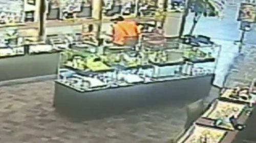 The footage shows a man, wearing a high-viz vest, jump the counter and smash the display cabinet before scooping jewellery into a bag.