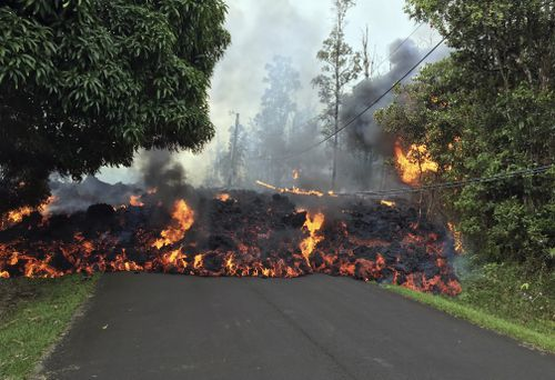 A lava flow moves across Makamae Street in the Leilani Estates subdivision near Pahoa on the island of Hawaii. (AP)