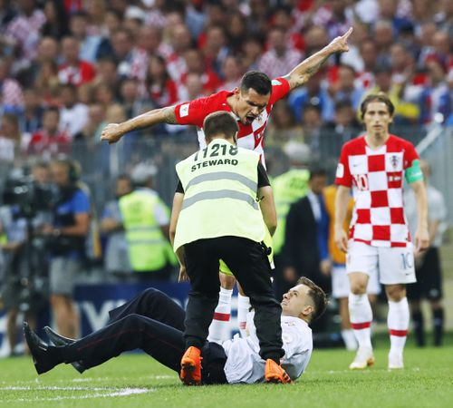Dejan Lovren (top) of Croatia yells at an intruder (bottom) during the second half of the World Cup final against France at Luzhniki Stadium in Moscow on July 15, 2018. Russian protest group and musical act Pussy Riot has claimed responsibility for the incident. (Kyodo via AP Images)