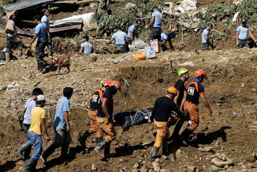 Rescuers carry a body they recovered at the site where victims are believed to have been buried by a landslide after Typhoon Mangkhut lashed Itogon, Benguet province, northern Philippines.