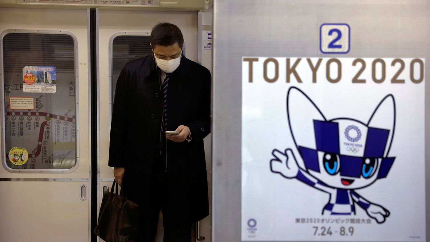 A poster promoting the Tokyo 2020 Olympics is posted next a train door as a commuter wearing a mask looks at his phone in a train