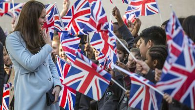 The Duchess is greeted by students with flags. (AAP)